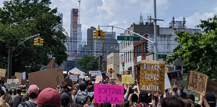 Street filled with people holding signs and marching in support of the Movement for Black Lives